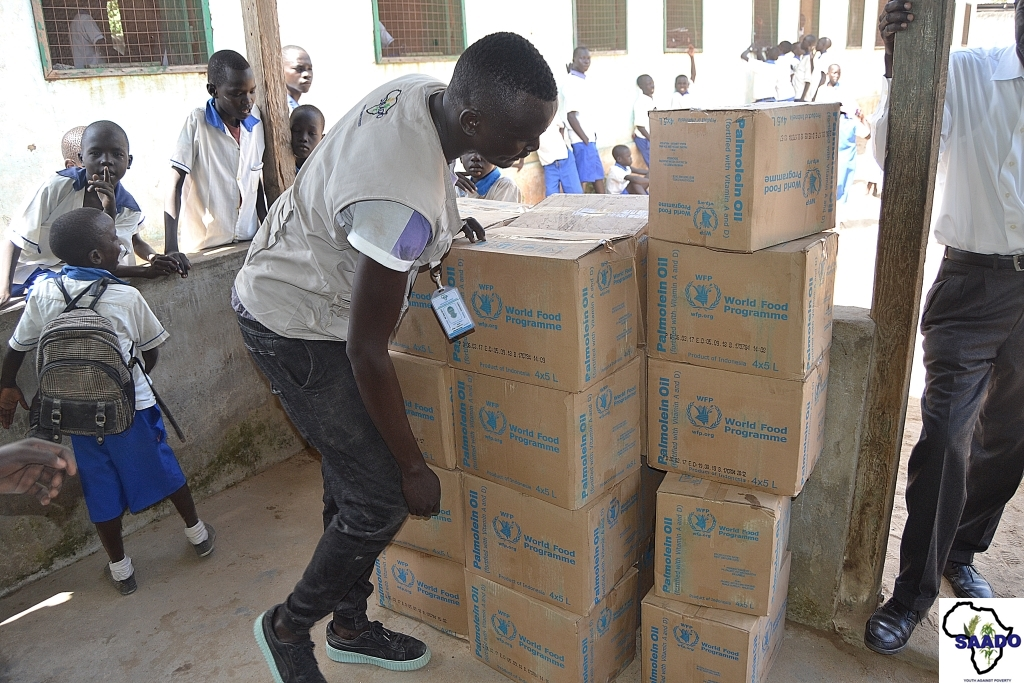 A SAADO Field Officer counting boxes of cooking oil during distribution at Malakia Primary School. Photo credit: SAADO